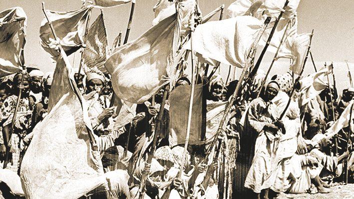 """Les femmes des tribus Smala agitent des drapeaux blancs pour demander l'""""Aman"""" (pardon) au gÈnÈral Franchi, commandant de la rÈgion militaire de Casablanca, le 28 ao˚t 1955, aprËs les massacres perpÈtrÈs le 20 ao˚t par les hommes de ces tribus ‡ Oued Zem, au Maroc. Les Èmeutes ont ÈclatÈ le jour anniversaire de la dÈposition par le gouvernement franÁais du sultan du Maroc, Mohammed ben Youssef."""