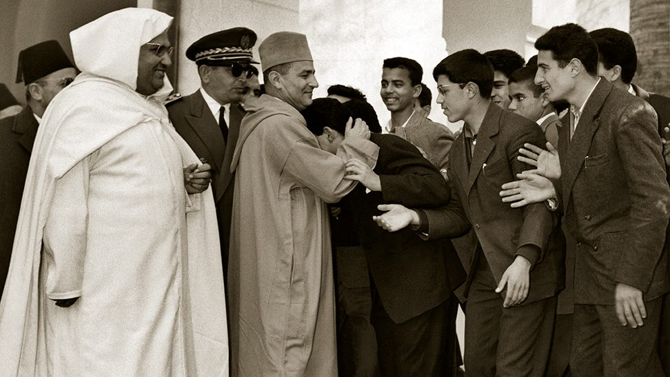 (FILES) A picture taken on January 27, 1958 shows Moroccan King Mohammed V (C) hugging a student as Education Minister Mohammed El Fassi looks on during King's visit to Moulay Idriss High school in Fez where he attends the UNESCO Congress of Arab states. AFP PHOTO