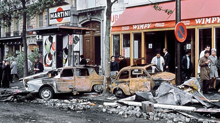 Des Parisiens regardent les voitures incendiÈes lors des violentes bagarres qui ont opposÈ des Ètudiants aux forces de l'ordre dans la nuit du 24 au 25 mai 1968 au quartier Latin ‡ Paris. / AFP PHOTO